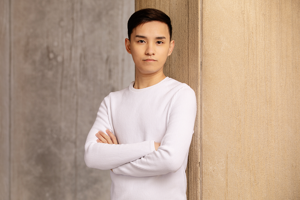 Portrait of Fan Xuan Chen. He is standing with arms crossed.