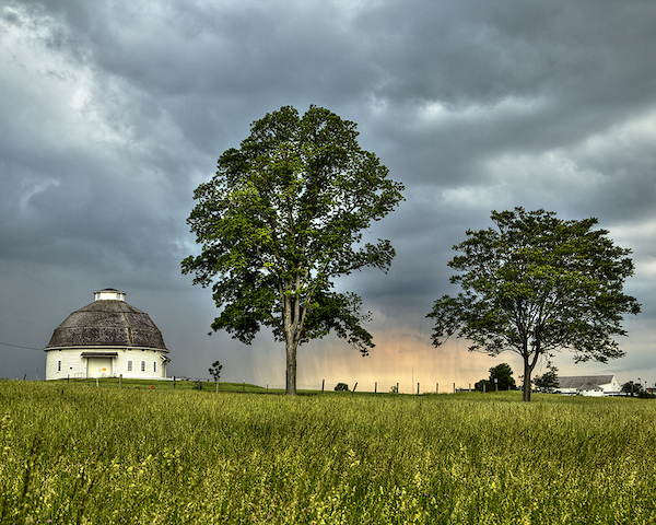 Storm clouds behind a round barn and tree