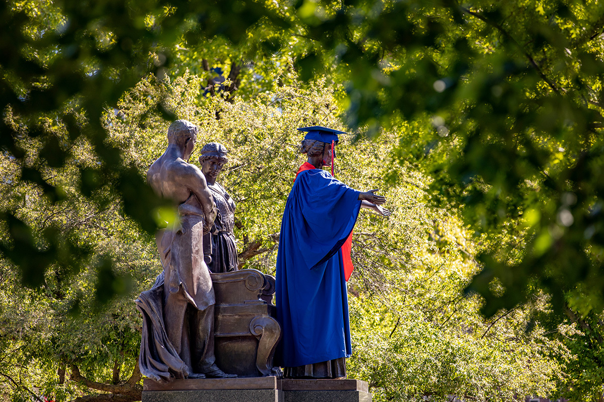 A side view of the iconic Alma Mater statue sporting graduation garb.