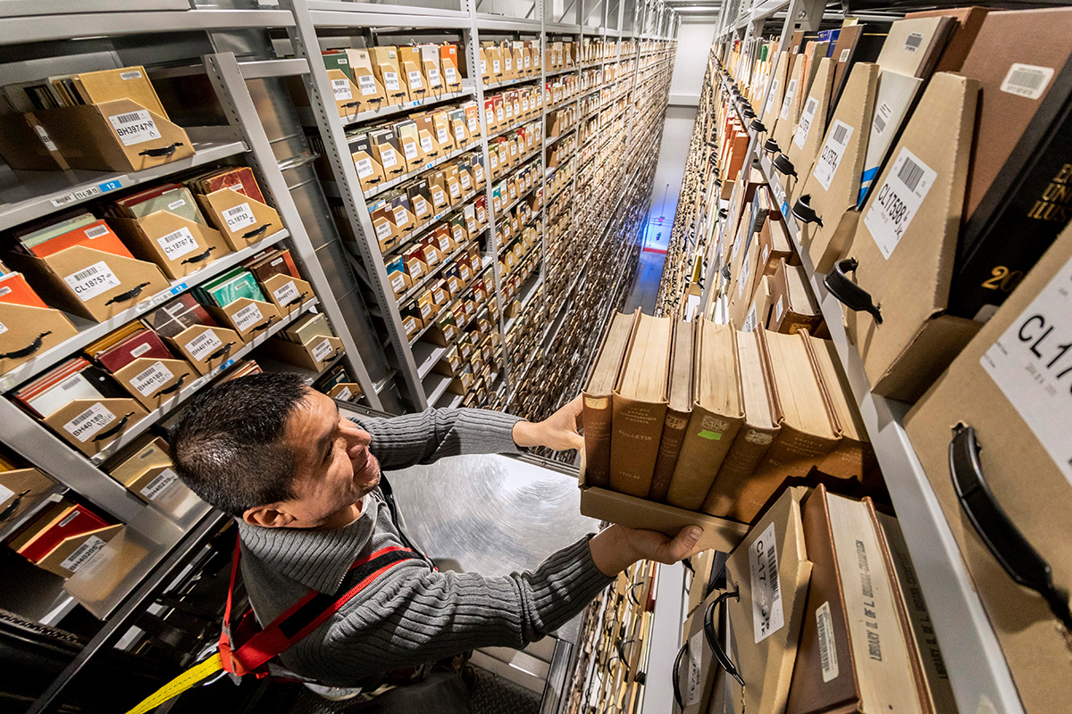 Image of facility coordinator Jimmy Gonzalez using a lift to shelve books at the top of the stacks.