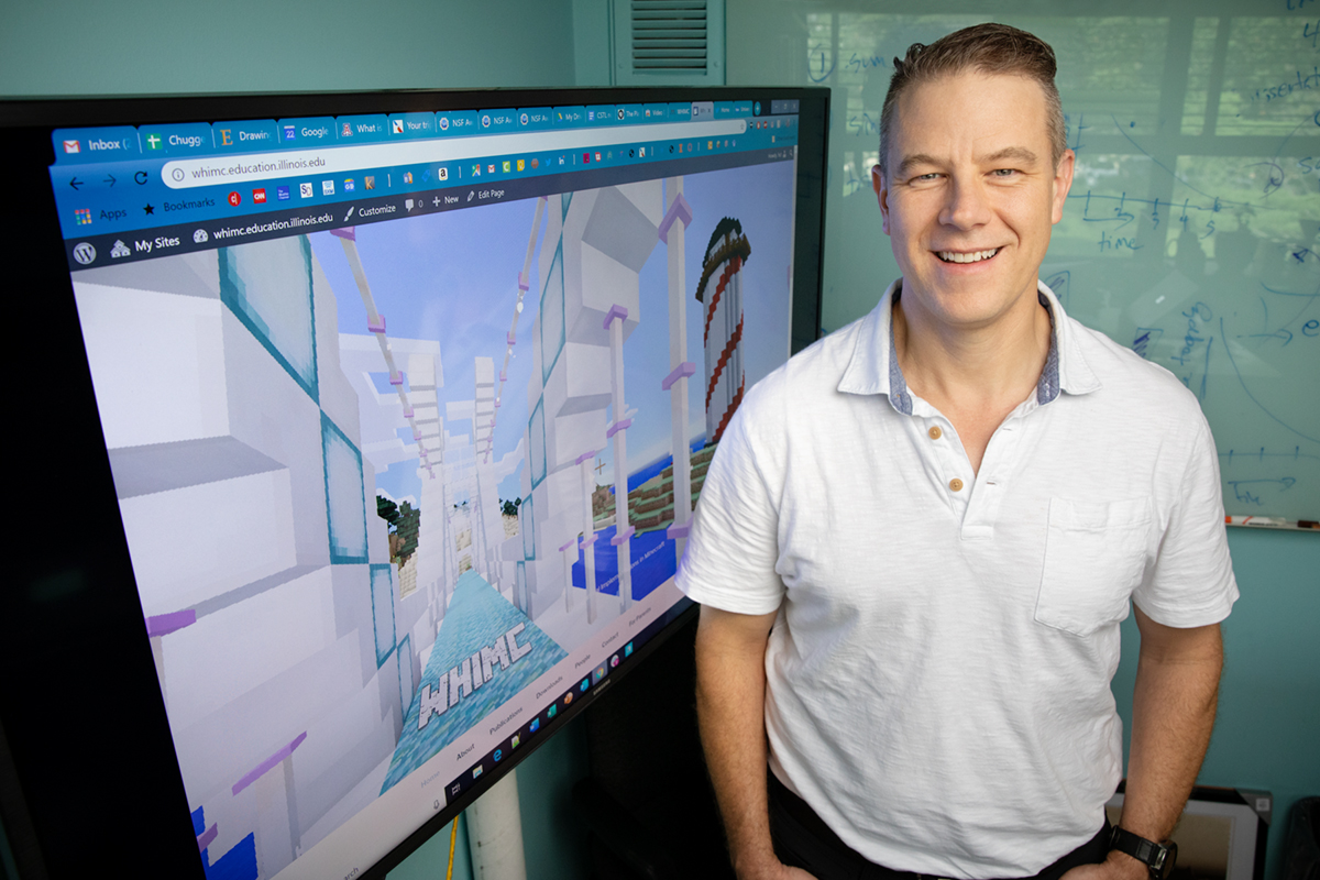 Photo of University of Illinois educational psychology professor H. Chad Lane standing by a screen displaying Minecraft