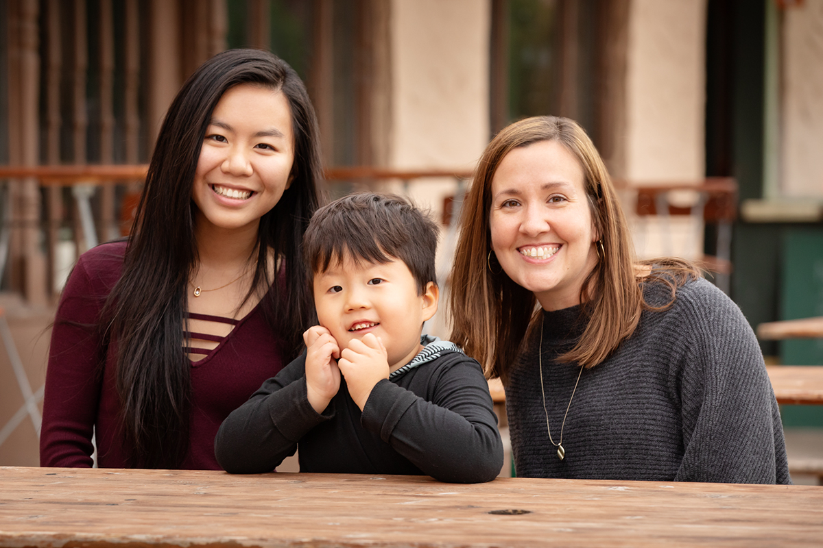 Photo of special education professor Meghan Burke, her son Rogan and Lily Ho, a senior in computer science