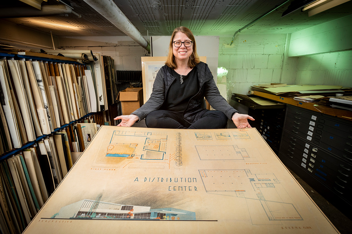 Architecture professor Marci Uihlein with a student drawing in the architecture department's student design archives.
