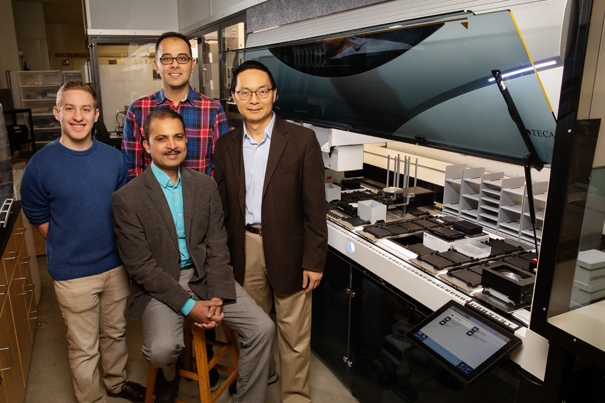 Scott Weisberg, left, professor Saurabh Sinha, seated, Mohammad (Sam) Hamedi Rad and professor Huimin Zhao have combined a fully automated robotic platform with artificial intelligence to develop a new way to manufacture chemicals.