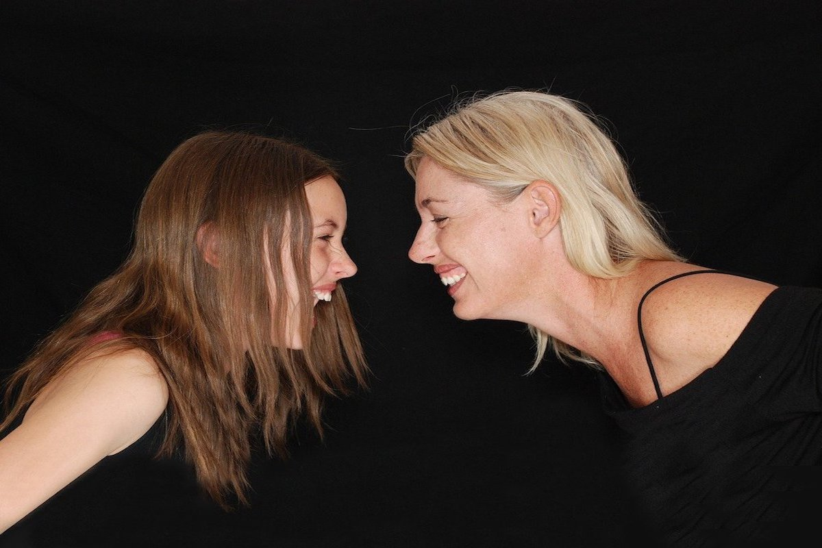 Photo of mother and daughter bending toward each other and smiling widely