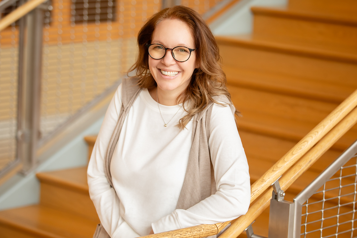 Photo of U. of I. professor Karen Kramer standing at the bottom of a stairway and leaning on one elbow on the railing