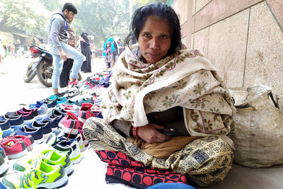 A female vendor in a mahila bazaar in New Delhi stares solemnly at the camera. A young man in the background is looking at the wares of a nearby vendor.