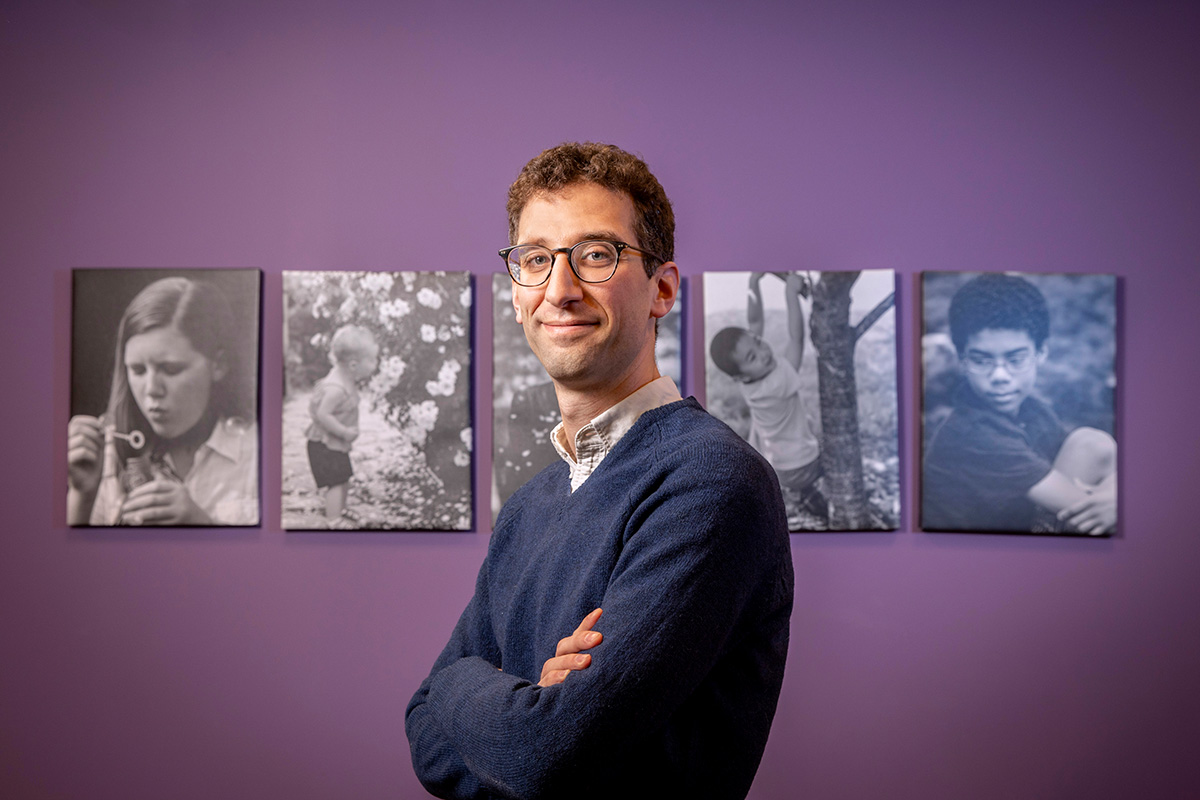 Photo of social work professor Will Schneider standing with arms crossed in front of the logo at the School of Social Work