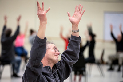 Gary Stitt, 61, stretches his arms to the sky as people gather for a Dance for People with Parkinson's class at Krannert Center.