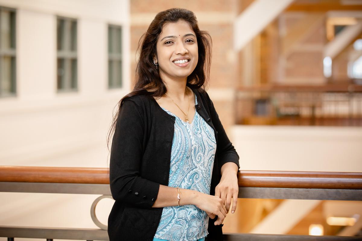 Professor Lavanya Marla stands at the rail of a sunlit atrium overlook in a campus building.