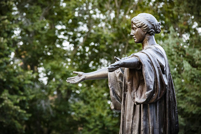Photo of the bronze statue of Alma mater with her arms outstretched in a welcoming gesture.