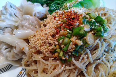 A heap of thick noodles is topped with a pile of crushed peanuts, scallions and red chili.