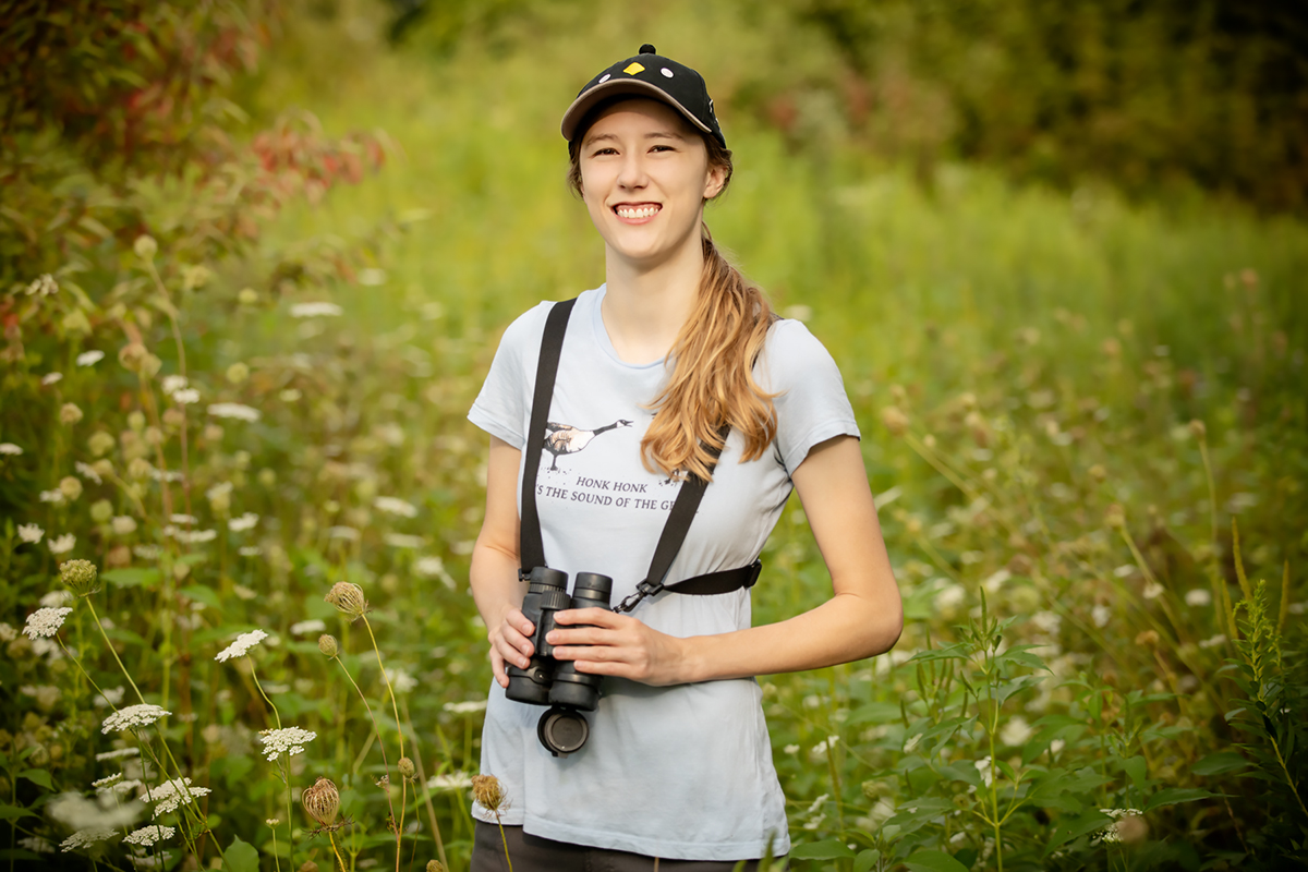 Shelby Lawson stands in a grassy area with binoculars around her neck.