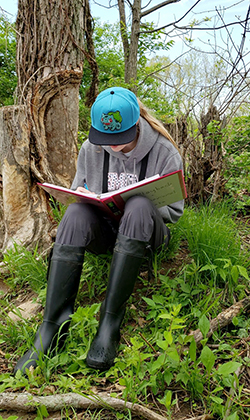 Lawson sits under a tree and writes in a field notebook.