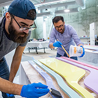 Two people fabricating mural pieces for Siebel Center for Design