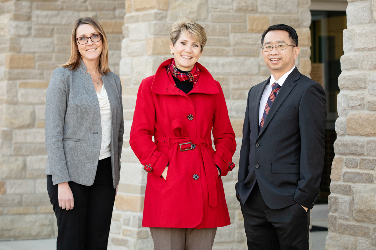 U. of I. social work professor Kevin Tan standing outside the Mahomet-Seymour School District building with director of instruction Nicole Rummel and superintendent Lindsey Hall, both of Mahomet-Seymour school district.