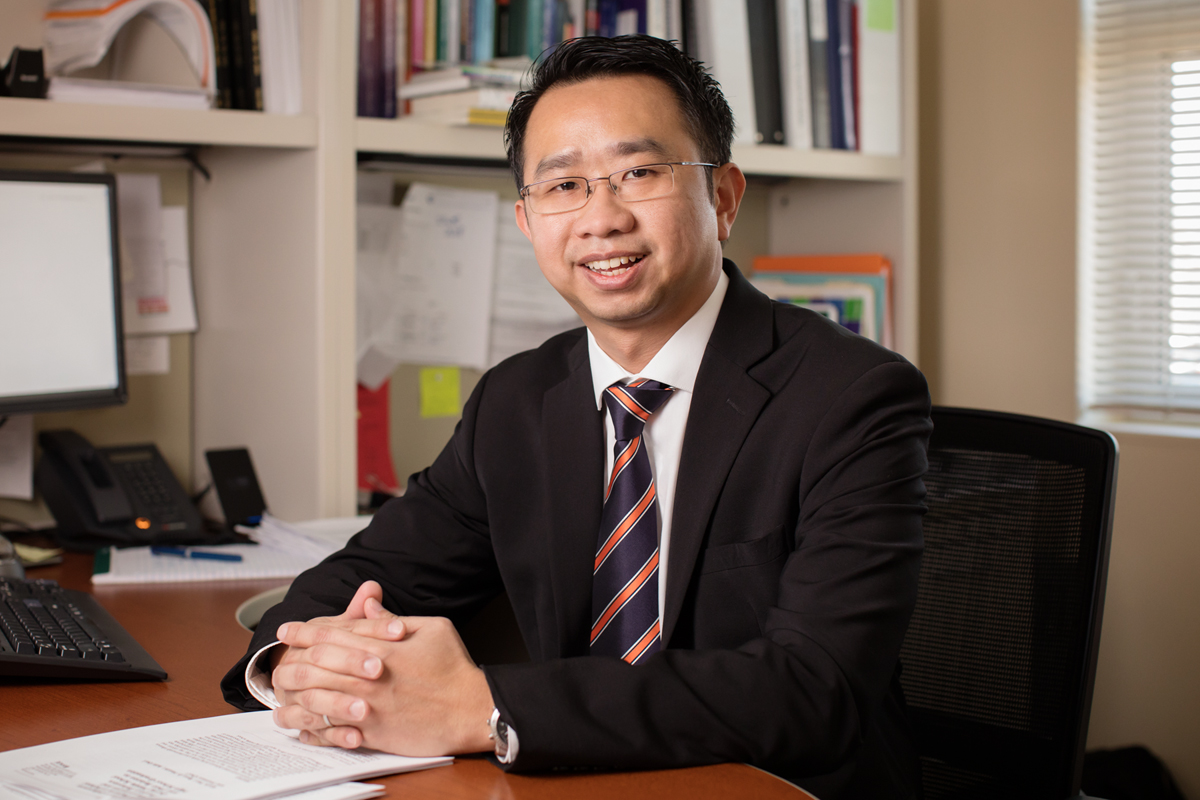 Social work professor Kevin Tan sitting at his desk in his office on the University of Illinois campus